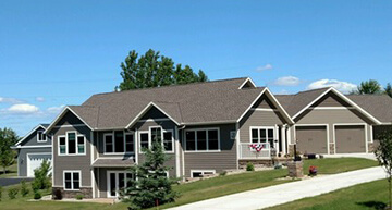 Large custom single family home with grey siding and white trim taken in summer with blue skies | Residential Services