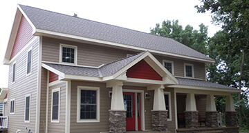 Exterior of a newly remodeled home featuring maintenance-free siding, new windows, and stone facade | Remodels