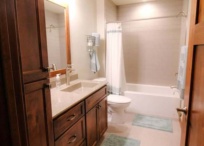 Luxury bathroom with tile shower, stone countertops and a wood vanity | Bathroom Renovation Services