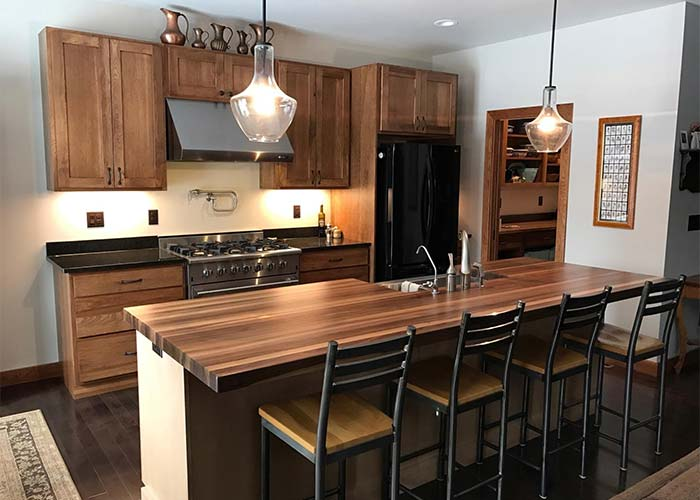 Custom Kitchen with medium-dark wood cabinets, a butcher block island, and hanging pendent lights | Kitchen Remodeling Services